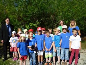 Die Klasse 1 bis 2 der Grundschule Oggenhausen freut sich über ihr neues Klassenmaskottchen zusammen mit Dieter Henle und der Leitung des Grünen Klassenzimmers Kirsten Schröder-Behrendt.